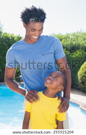 Happy father and son smiling at each other in the garden at home