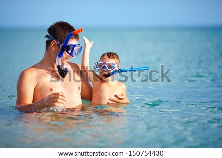 happy father and son snorkeling - stock photo