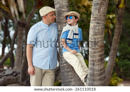 Happy father and son talking and having rest outdoors during his summer vacation - stock photo