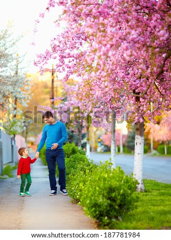 happy father and son walking the spring street - stock photo