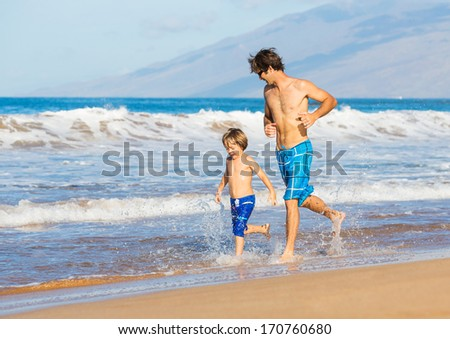 Happy father and son walking together on the beach, carefree happy fun smiling lifestyle - stock photo