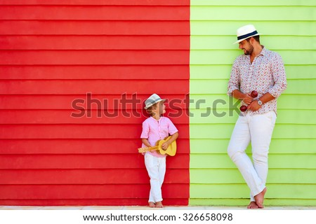 happy father and son with musical instruments near the colorful wall