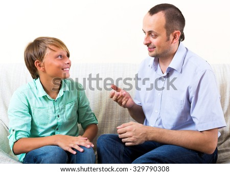 Happy father and young son discussing something interesting indoors at home - stock photo