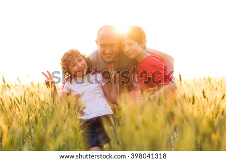 Happy father, brother and sister, little boy and girl outdoors on the nature field in sunlight. Children, kids outdoors on summer sunset. Family portrait smiling, spending time together outside. - stock photo