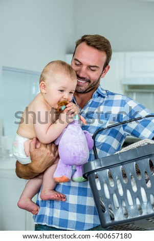 Happy father carrying playful son while holding basket in kitchen - stock photo
