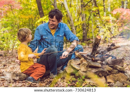 Happy father doing barbecue with his son on an autumn day.