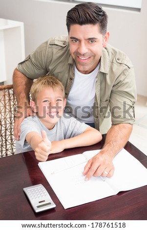 Happy father helping son with his math homework at table at home in kitchen - stock photo