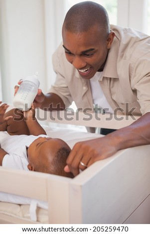 Happy father holding bottle for baby son at home in the bedroom - stock photo