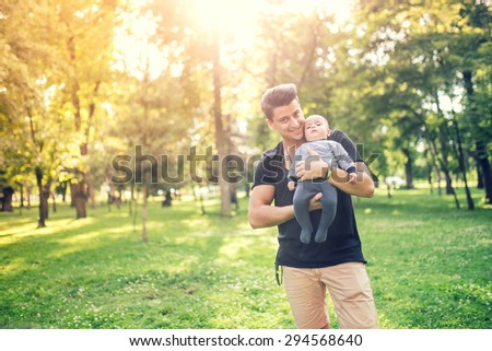 Happy father holding little son, infant boy on a sunny day in park.  - stock photo