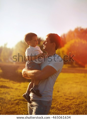 Happy father holding on hands child son warm autumn evening, sunny family photo, sunlight on sunset