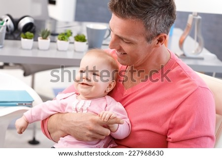 Happy father holding on lap happy baby daughter, both smiling. - stock photo