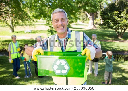 Happy father holding recycling case on a sunny day - stock photo