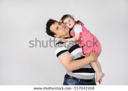 Happy father holds and hugs her little cute daughter on grey background.