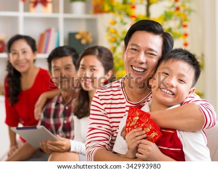 Happy father hugging his son who is holding lucky money envelopes - stock photo
