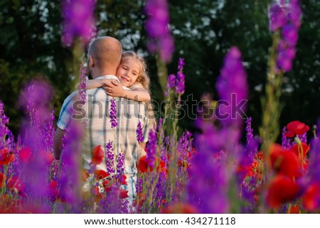 Happy father hugging little daughter in blossoming field - stock photo