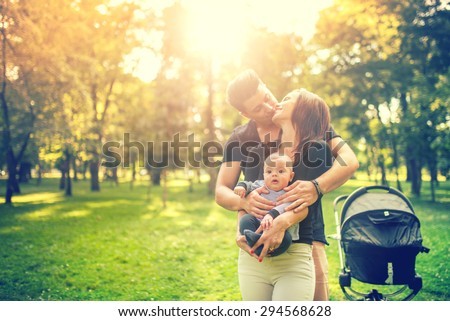 Happy father hugging mother and holding delicate newborn in arms. Happiness in family concept - stock photo