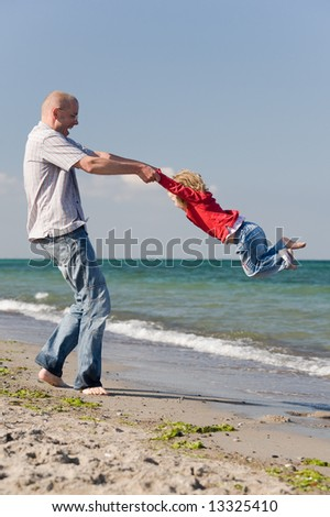 Happy father is playing with his daughter at the beach - stock photo