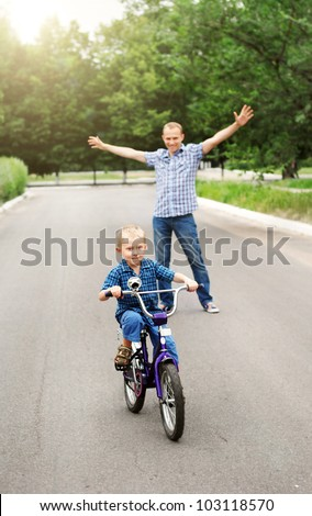 Happy father is train his son to ride a bicycle - stock photo
