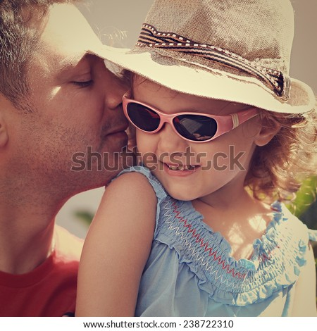 Happy father kissing his daughter in fashion glasses and hat outdoors - stock photo