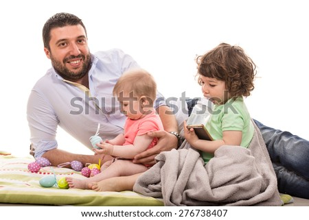Happy father laying together with his baby daughter and toddler boy