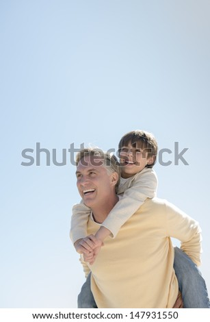 Happy father looking away while giving piggyback ride to son against clear blue sky - stock photo