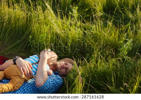 happy father lying on the grass with his son on the chest - stock photo
