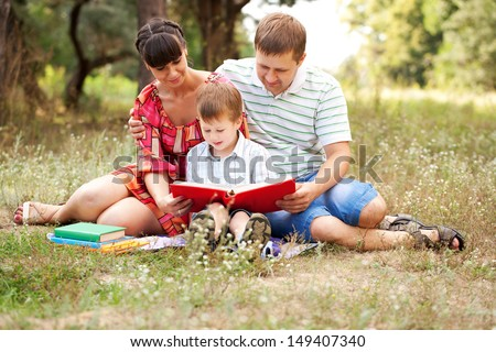 Happy father, mother and son reading book on the lawn in the park. Family reading together. Summer holiday. Happy family concept.