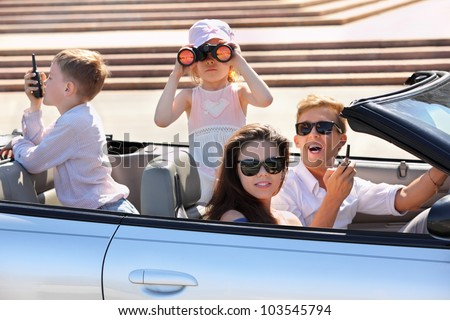 Happy father, mother and two children ride in convertible car and play spies at sunny day; focus on woman - stock photo