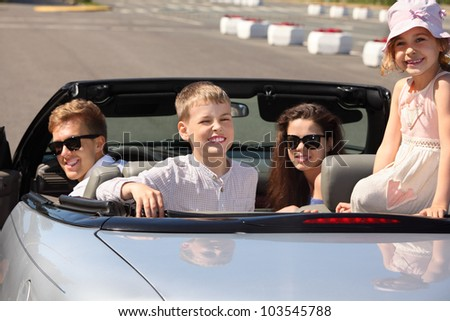 Happy father, mother and two children sit in convertible car and look back; focus on children - stock photo