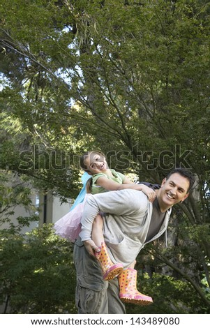 Happy father piggybacking cheerful little girl in park - stock photo