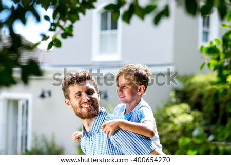 Happy father piggybacking son while standing in yard - stock photo