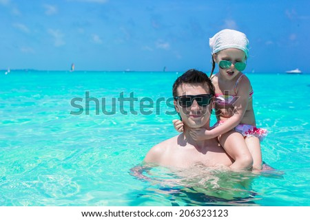Happy father play with little daughter in the sea