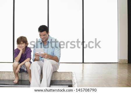 Happy father playing handheld video game sitting next to son at home - stock photo