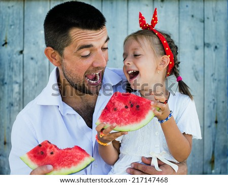 happy father playing with cute little daughter holding  watermelon - stock photo