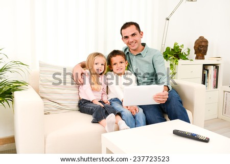 Happy father playing with digital tablet with his children in a sofa at home