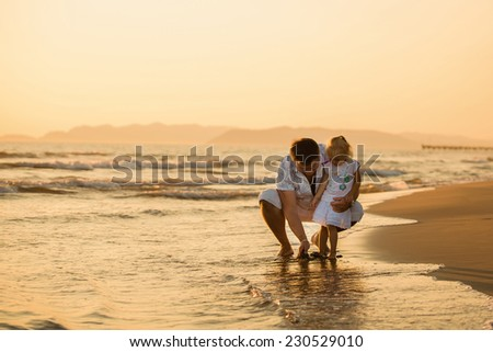 Happy father playing with his daughter by the seaside at sunset, summer time. Fatherhood concepts, Italy, Forte dei Marmi - stock photo