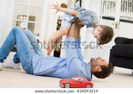 Happy father playing with son while lying on the floor at home. Young man playing with small boy. Flying child enjoying playing with dad. - stock photo