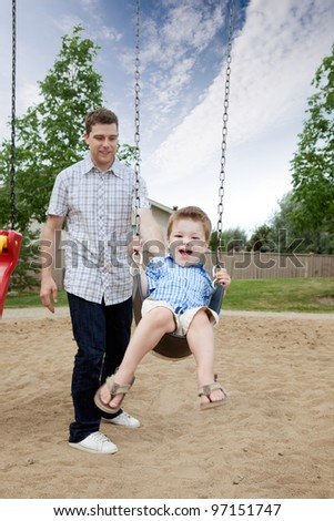 Happy Father Pushing Boy On Swing In Playground.