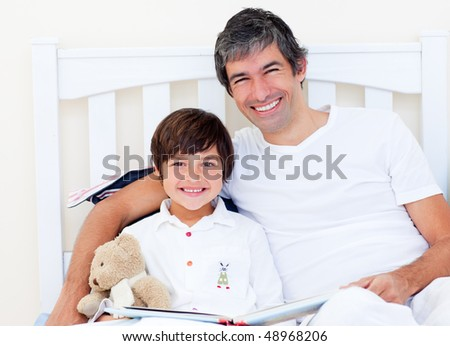 Happy father reading with his son sitting on a bed - stock photo