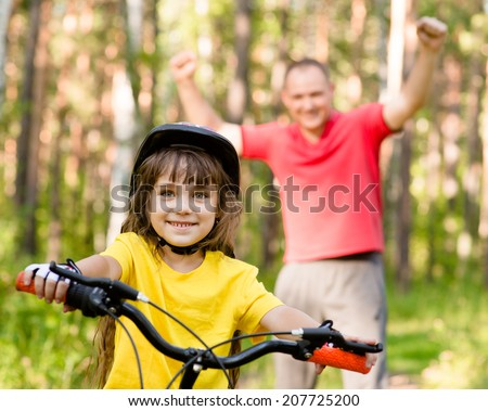 happy father rejoices that her daughter learned to ride a bike - stock photo