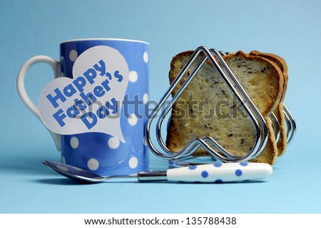 Happy Father's Day breakfast message on white heart tag with polka dot coffee mug and heart rack with wholemeal toast on blue background. - stock photo