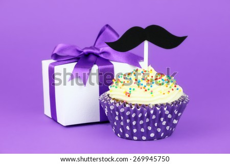 Happy Father's Day greeting with a gift box tied with purple ribbon and a cupcake decorated with buttercream frosting, colourful sprinkles and a black hipster mustache topper - stock photo