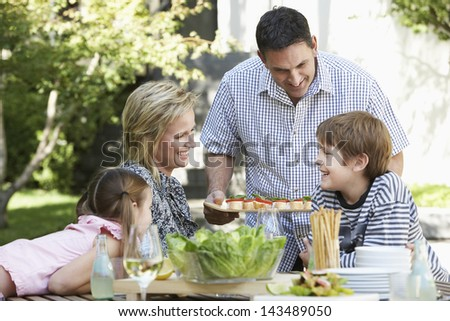 Happy father serving food to family at picnic table in park - stock photo