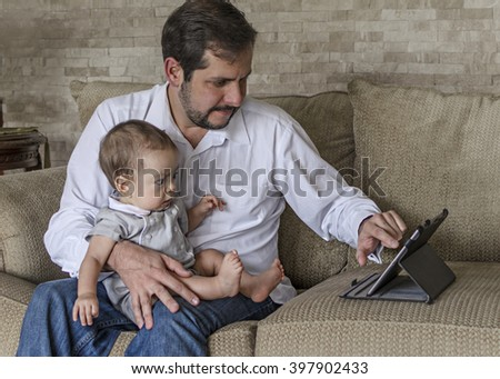 Happy father siting in sofa with beautiful baby son, using tablet pc.