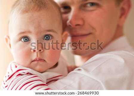 Happy Father sitting with baby in her arms