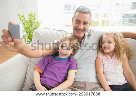 Happy father taking selfie with children on sofa at home - stock photo