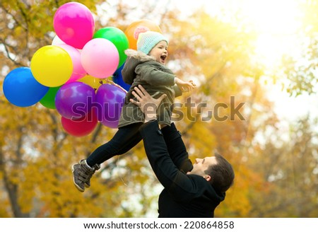 happy father toss up little child with air-balloons, outing in autumn park - stock photo