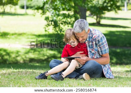 Happy father using tablet pc with his son on a sunny day - stock photo