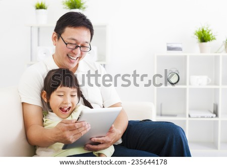 happy father using tablet pc with little girl - stock photo