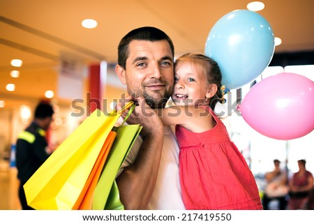 happy father with cute little daughter shopping in mall - stock photo
